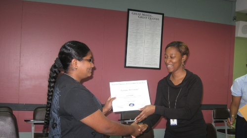 ABE Business Management Level 4 student, Ms. Farnaaz Mohammed, smiles as she accepts her certificate from Senior Academic Administrator, Ms. Patrice Belfon