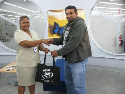 Sharon Beharry, Library Assistant, Champs Fleurs campus, presents Raymond Law with the SBCS token.